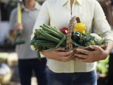 Woman holding basket of vegetables, close up, mid section