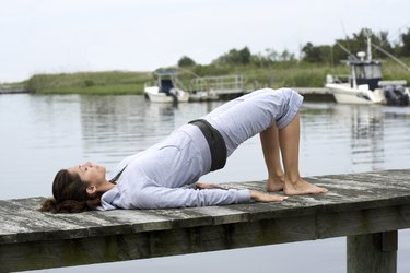 Woman exercising on pier