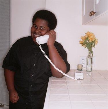 Teenage boy (16-17), talking on telephone in home, portrait