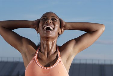 Young female athlete with hands behind head laughing