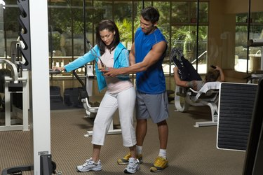 Man instructing to woman in gym