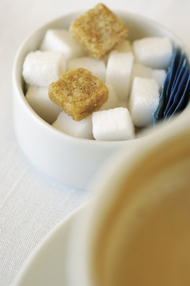 Sugar bowl with sugar cubes next to cup of cappuccino