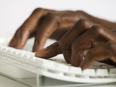 Close-up of a man's hands working on a computer keyboard