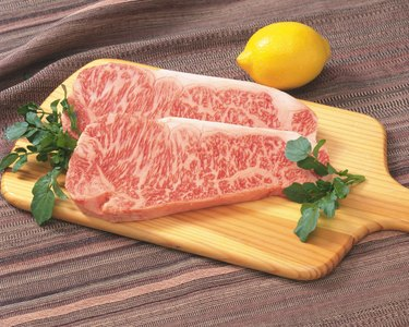Sir Loin steaks on cutting board with lemon, high angle view, close up