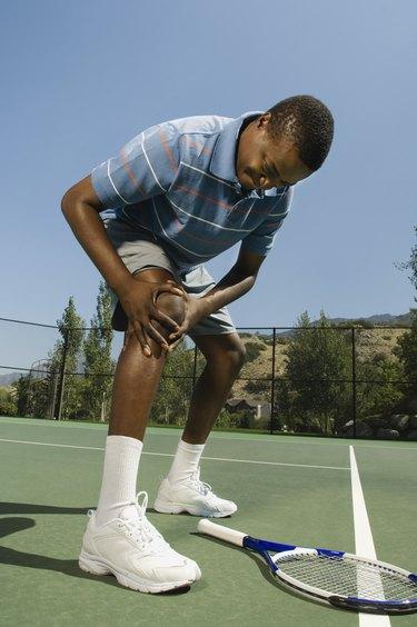 Tennis player holding injured knee
