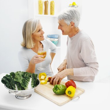 mature man chopping peppers talking to a mature woman who is drinking a glass of white wine