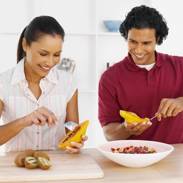 Smiling young couple preparing fruit together