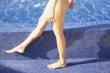 Close up of woman's legs walking next to pool