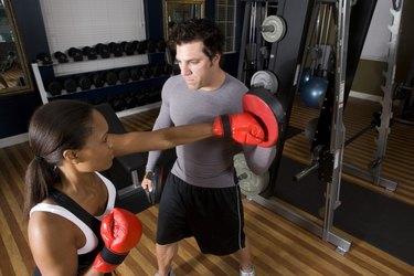Trainer instructing a young woman with boxing equipment in the gym