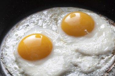 Closeup photo of two scrambled eggs in black frying pan