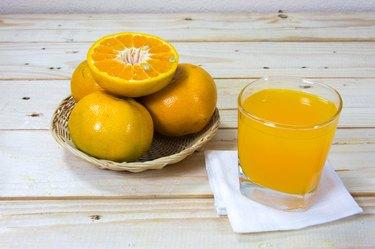 Glass of orange juice and slices of orange on wooden