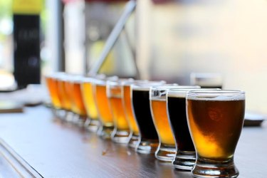 Craft beers in taster glasses are lined up on a bar counter for a beer tasting.
