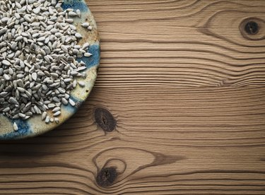 Sunflower seeds on plate against wooden background