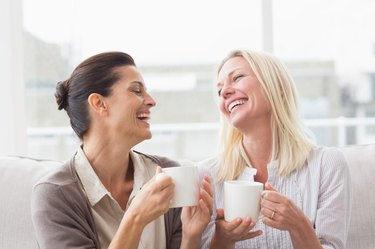 Women gossiping while having coffee in living room