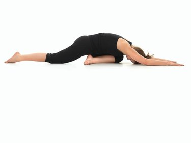 young girl in yoga pose, side view, dressed in black, on white background