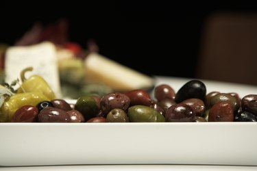 Olives, peppers and cheese on table (focus on olives in foreground)