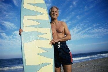 Senior man holding a surfboard