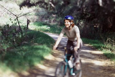 Woman riding mountain bike on a trail