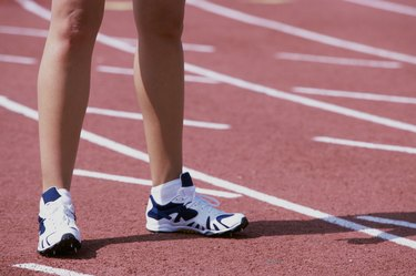Low section view of a female athlete standing on a running track
