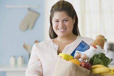 Hispanic woman holding bag of groceries