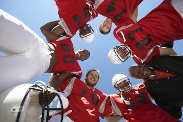 Football Players and Coach in Huddle