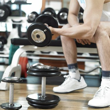 a man exercising with dumbbells at a fitness club