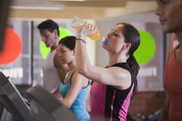 Woman drinking sports drink on treadmill