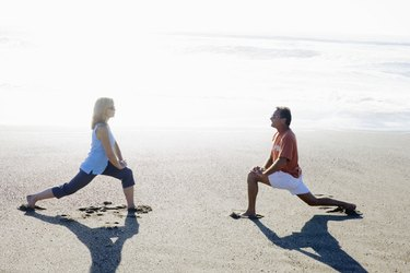 Couple stretching on beach