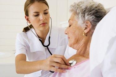 Nurse checking woman's heartbeat