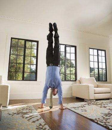 Hispanic businessman doing handstand