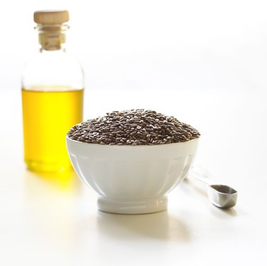 Flax seed and olive oil with measuring spoon
