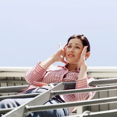 Low angle view of a young woman leaning over a railing holding her head