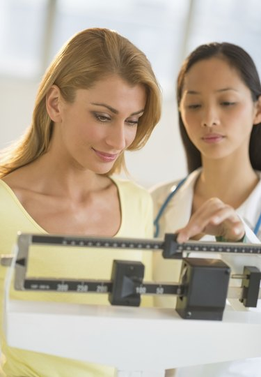Doctor Weighing Woman On Balance Weight Scale