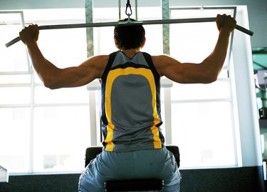 Rear view of a young man exercising on an exercise machine
