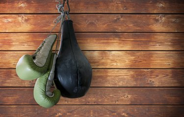 old boxing gloves and punching bag hang on wooden background