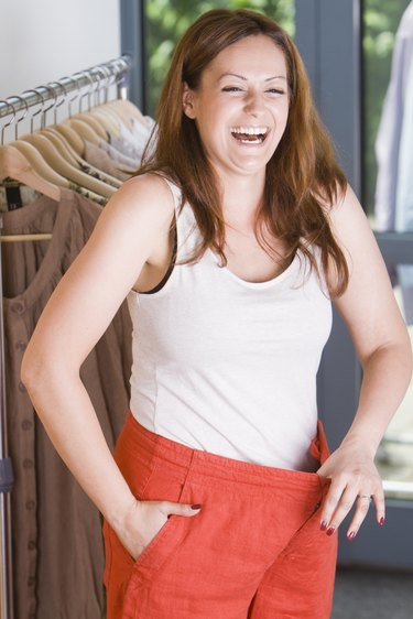 Young woman trying on large pair of red trousers in store