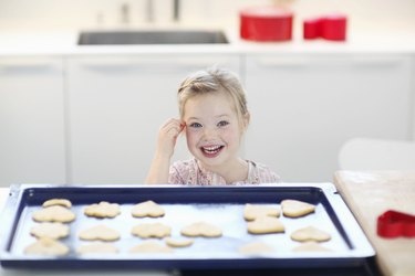 Girl with cookie dough on baking tray