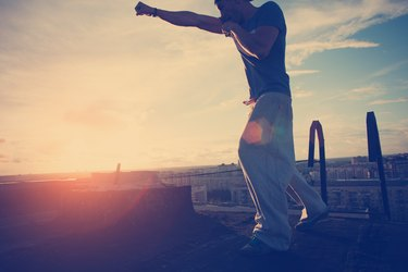 Young man boxing with shadow at sunset on the top of the roof in the city (intentional sun glare, lens flares and vintage color)