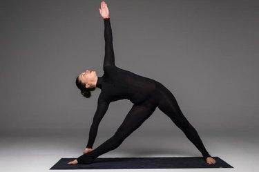 Trikonasana. Beautiful yoga woman practice yoga poses on grey background. Yoga concept.