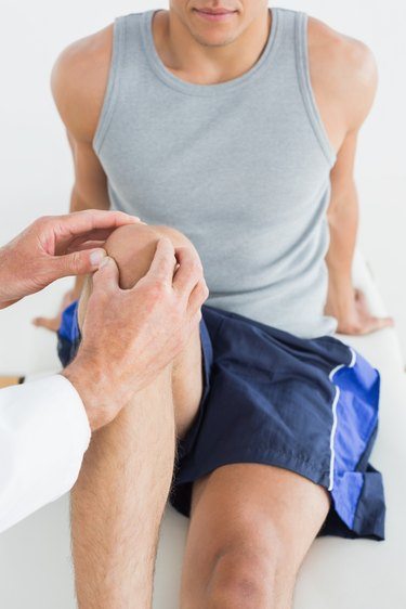 Close-up of a man getting his knee examined