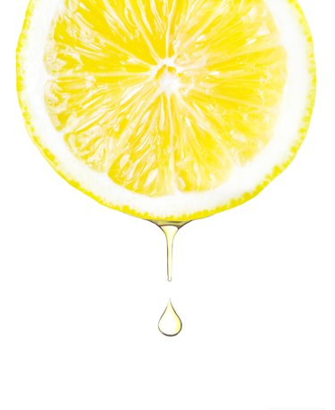 Sliced lemon with juice dropping. Isolated on white