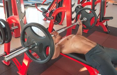 mature strong man in gym exercising on the bench press