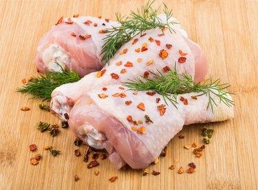 Three chicken legs sprinkled pepper on bamboo board