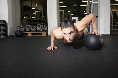 Athlete performing one-handed push up on a medicine ball at the gym.