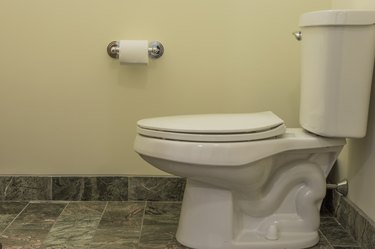 Toilet seat with toilet paper on tiled floor