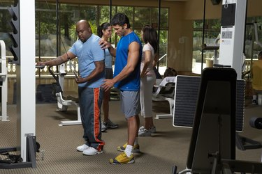 People working out in gym, side view