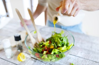 hand pouring olive oil into salad on wooden table