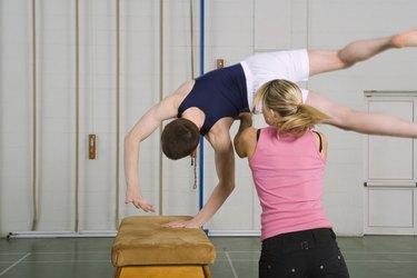 Coach helping gymnast cartwheel