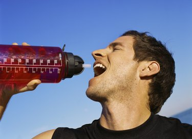 Side profile of a mid adult man drinking an energy drink