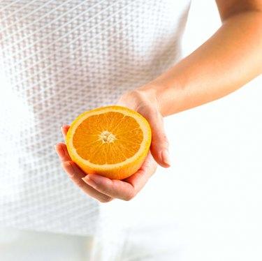 Hands holding orange half